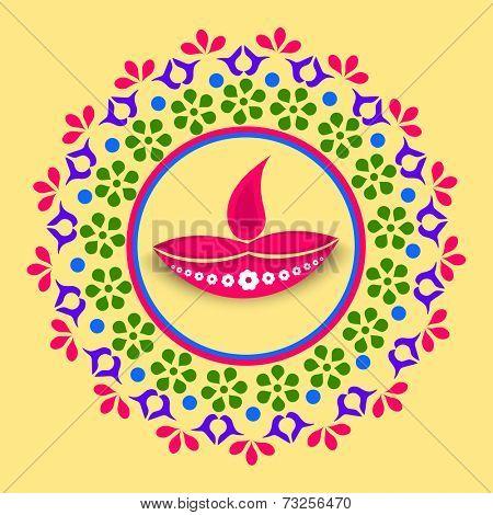 Stylish colorfull rangoli with illuminated oil lit lamp for diwali celebration on yellow background.