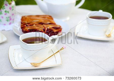 Teacups and tasty pie on table, close-up, in garden