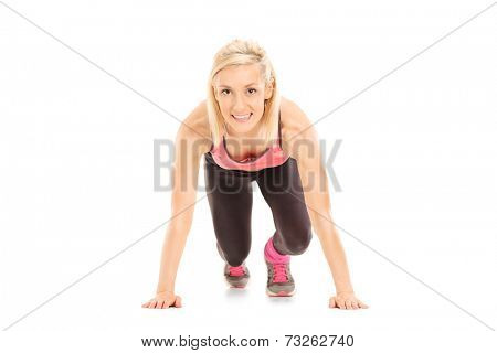 Female sprinter in starting position isolated on white background