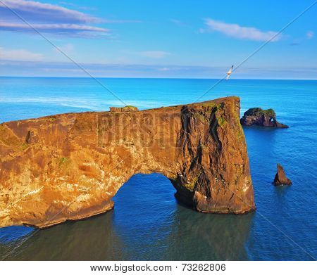Cape Dirholaey in southern Iceland. Sunset in July. Colossal rock- elephant lit sunset