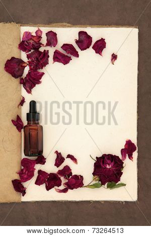 Rose flower and petals with aromatherapy essential oil bottle on an old vintage notebook over lokta paper background.