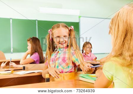 Smiling girls turned to classmate giving pencil
