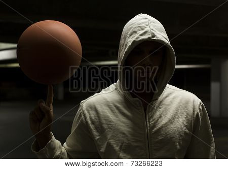 Hooded basketball player spinning a basketball