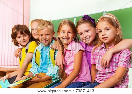 Group of children stand close to each other hug