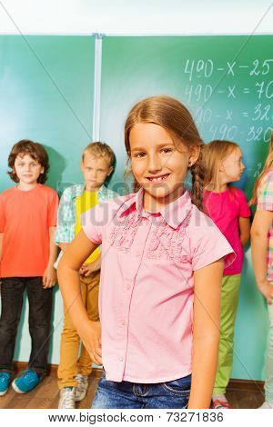 Smiling girl stands near green blackboard