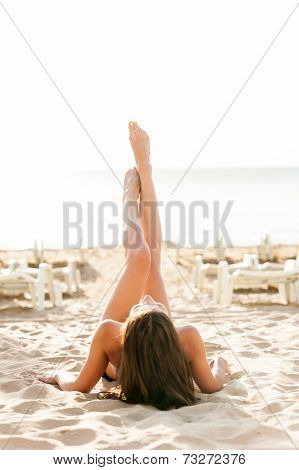 Beautiful woman with legs raised up high in the air.