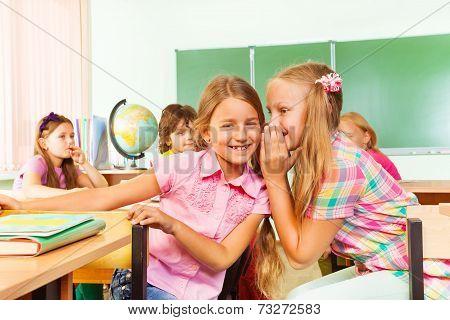 Beautiful girl tells secret to other in school