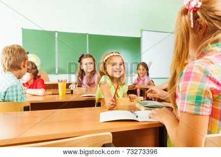 Happy pupils in classroom sitting at desks