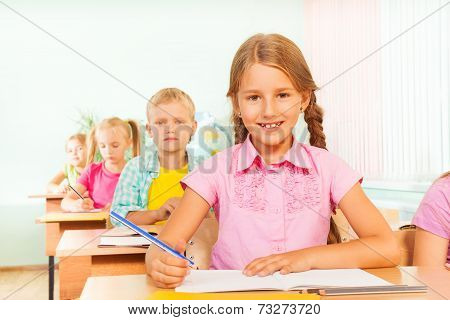 Cute girl smiles, sits at desk and writes