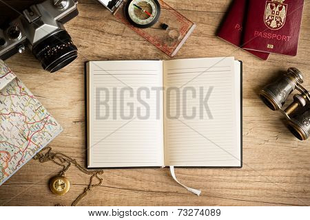 Old notebook, compass, map, vintage binoculars, photo camera on wooden background