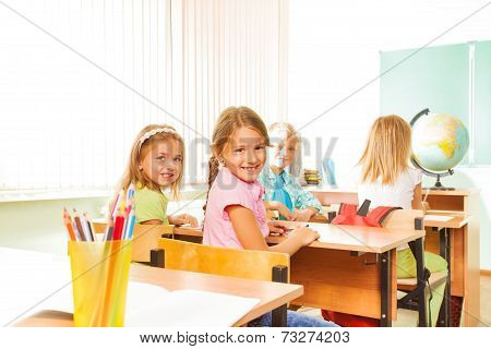 Happy girls looking and sitting in rows at desks