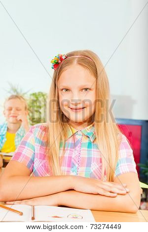 Girl sits at desk with hands on exercise book