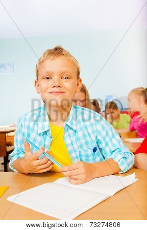 Smiling boy looks while writing in exercise book