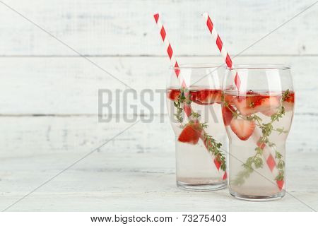 Tasty cool beverage with strawberries and thyme, on wooden background