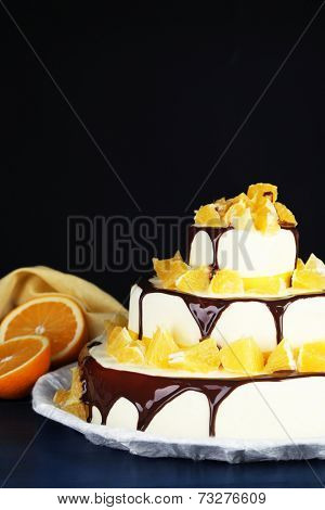 Beautiful wedding cake with oranges and chocolate on dark background