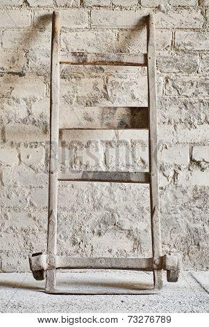 grunge wall, vintage two wheels barrow for carrying grain sacks