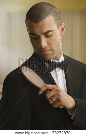 Hispanic man brushing lint off tuxedo