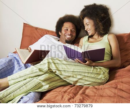 African couple reading in bed
