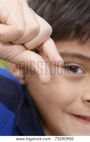 Hispanic boy holding out thumb and forefinger