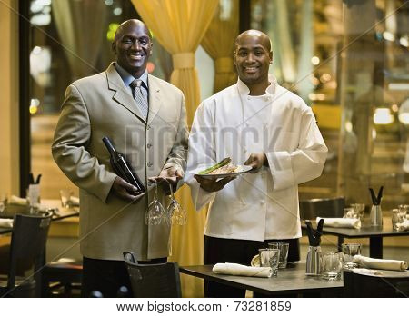 African male restaurant staff holding food and wine