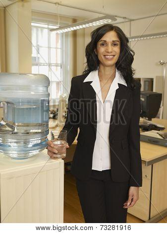 Hispanic businesswoman standing next to water cooler