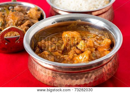 Indo-Chinese chili garlic chicken, a North Indian fusion food from Kolkata, with rice and Malabar chicken behind