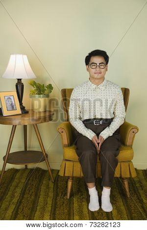 Nerdy Asian man sitting in armchair