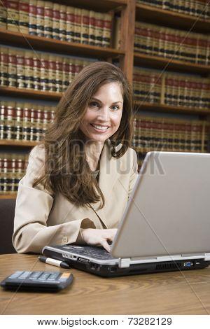 Hispanic woman typing on laptop