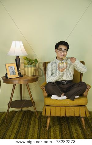Nerdy Asian man eating in chair