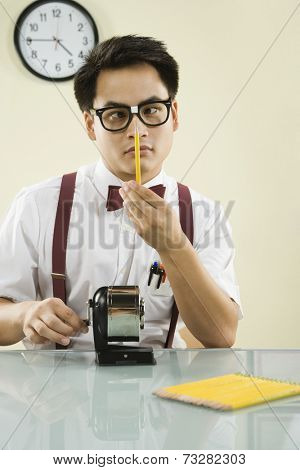 Nerdy Asian man sharpening pencil