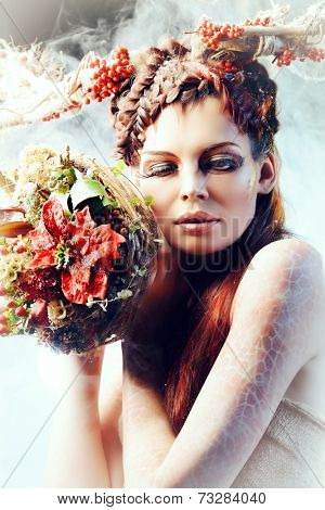 Art project. Close-up portrait of a beautiful girl in the image of a wood nymph holds winter bouquet.