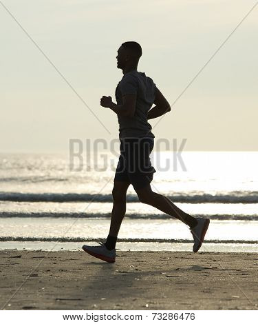 Young Man Running On The Beach By Water