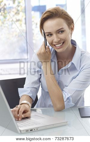 Closeup portrait of happy young woman talking on mobilephone, using laptop computer.