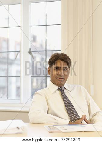 Indian businessman with paperwork at table