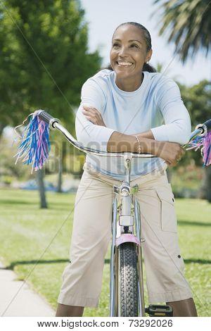 Mixed Race woman on girl's bicycle