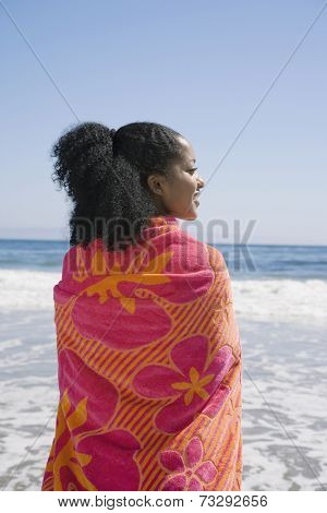 African woman wrapped in beach towel