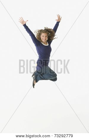 Teenager jumping with arms raised