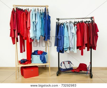 Wardrobe with red and blue clothes hanging on a rack nicely arranged.