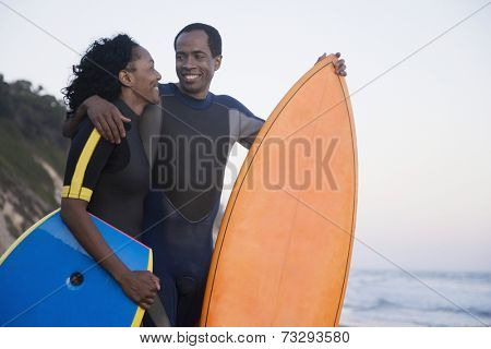 African couple holding surfboard and boogie board