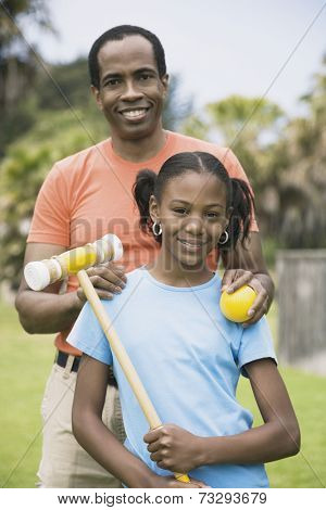 African father and daughter with croquet ball and mallet