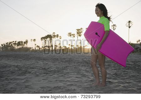Asian woman holding boogie board