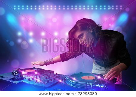 Pretty young disc jockey mixing music on turntables on stage with lights and stroboscopes