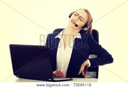 Young attractive business woman at call center is having backache. Isolated on white.