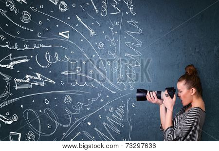 Photographer girl shooting images while energetic hand drawn lines and doodles come out of the camera