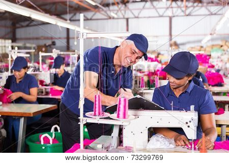 senior textile factory supervisor taking score from machinist