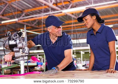 friendly senior cutter teaching young worker cutting fabric