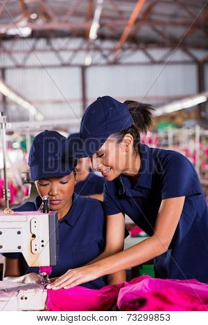 friendly young woman teaching new machinist to sew