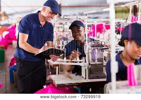 senior supervisor taking score from machinist in clothing factory