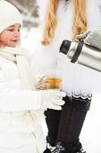 stock photo of thermos  - Happy young mother with daughter with thermos on winter picnic  - JPG
