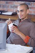 picture of telecommuting  - African American man eating take out food - JPG